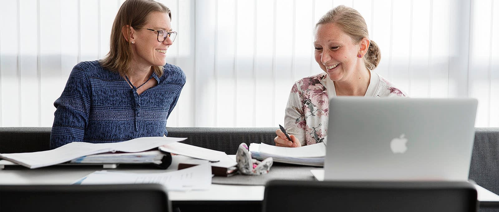 Två kvinnor ler mot varandra vid dator