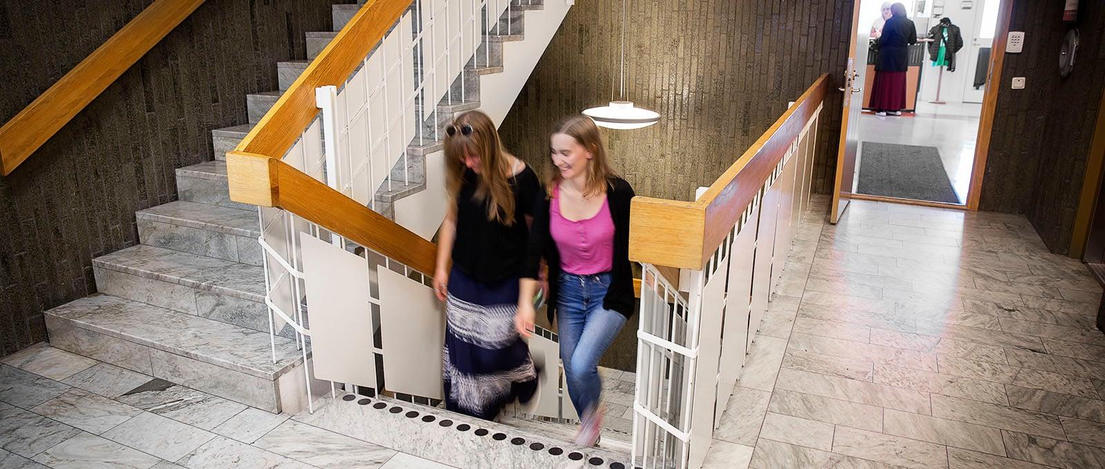 Två personer går i en trappa