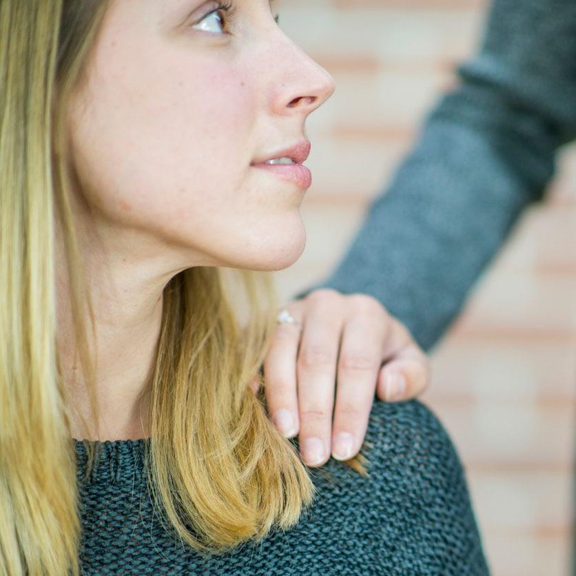 person som har en hand på sin axel